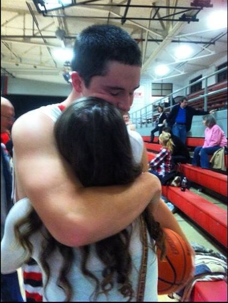 With one arm around the game ball and the other around his girlfriend Kylar Slover, Dakota Young savors the moment after the game.