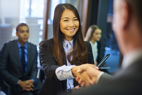young woman steps forward as she is called in for her interview and shakes hands with her possible new employer. Behind her other candidates wait with their resumes.